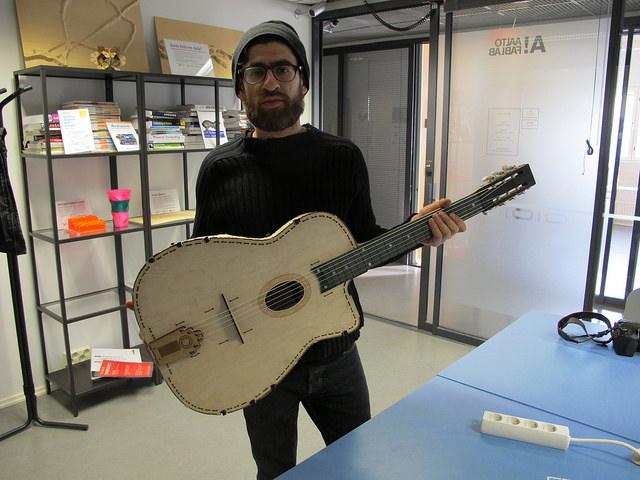 Kuva: Muotoilija, soitinrakentaja Ashkan Shabnavard ja tämän laserleikkurilla valmistama kitara (Aalto Fablab)