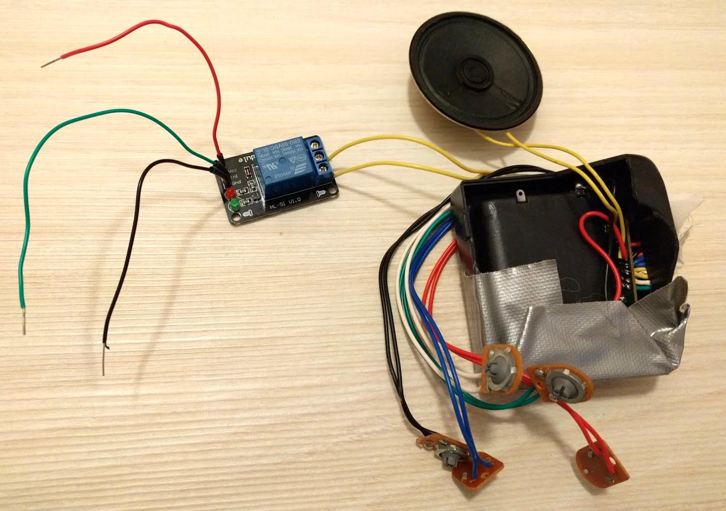 Kuvassa on puretun lelun elektroniikkaa. Lelussa on useita kytkimiä (harmaat napit ruskealla pohjalla). Yksi näistä on irrotettu ja jäljelle jääneet keltaiset johdot on kytketty releeseen. Lelussa on omat paristot sisällä.